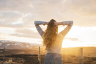 Iceland, young woman with hands in hair at sunset - KKAF01091