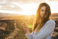 Iceland, woman using smartphone at sunset - KKAF01094