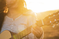 Iceland, woman playing guitar at sunset - KKAF01097