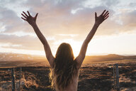 Iceland, young woman with raised arms at sunset - KKAF01106