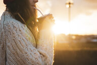 Iceland, young woman with coffee to go at sunset - KKAF01118