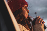 Iceland, young woman with coffee to go in the evening - KKAF01124