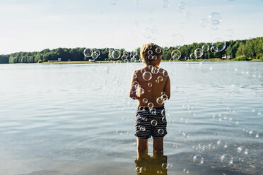 Boy in a lake surrounded by soap bubbles - MJF02255