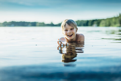 Portrait of happy boy in a lake holding tansparent sphere - MJF02261