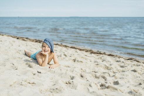 Portrait of happy boy lying on the beach - MJF02288