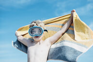 Boy with diving goggles and beach towel outdoors - MJF02291
