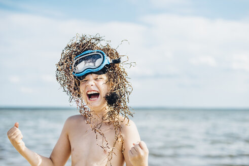 Carefree boy wearing seaweed wig on the beach - MJF02294