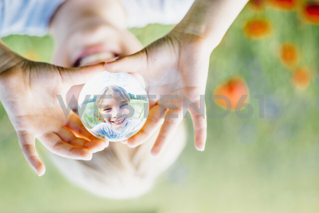 Reflection of smiling boy holding tansparent sphere in poppy field - MJF02303