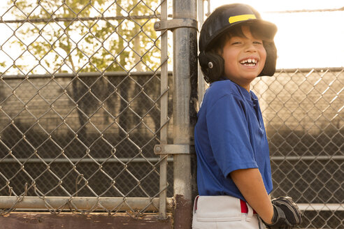 Laughing boy leaning against fence at baseball practise - ISF06575