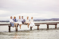 Group of friends, sitting in row on edge of pier - CUF17385