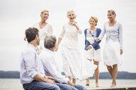 Group of friends on pier, female friends walking towards male friends sitting on edge of pier - CUF17388