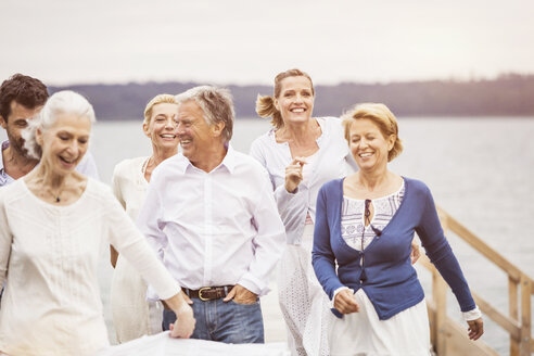 Group of friends walking together on pier - CUF17394