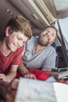 Mature man and teenage son reading map whilst lying in vehicle - CUF17415