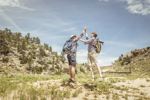 Hiking man and teenage son jumping to high five each other in landscape, Bridger, Montana, USA - CUF17436