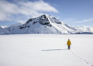 Woman enjoying snow-covered field, Litla-heidi, Iceland - CUF17451