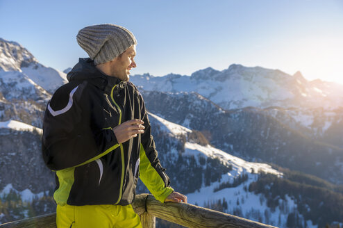Mid adult man on mountain wearing ski suit and knit hat looking away at view smiling, Jenner, Berchtesgadener, Germany - CUF17478