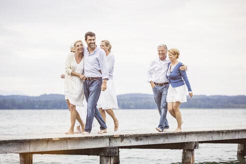 Group of friends standing walking along pier - CUF17493