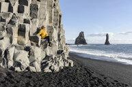 Woman on rock wall enjoying beach, Reynisfjara, Iceland - CUF17508