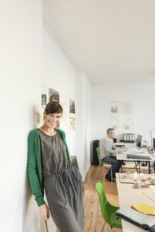 Mature woman in office leaning against wall looking at camera smiling - CUF17780