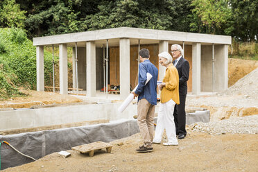 Couple on construction site discussing architectural foundations with architect - CUF17807