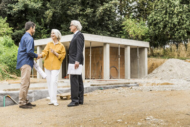 Couple on construction site shaking hands with architect smiling - CUF17810