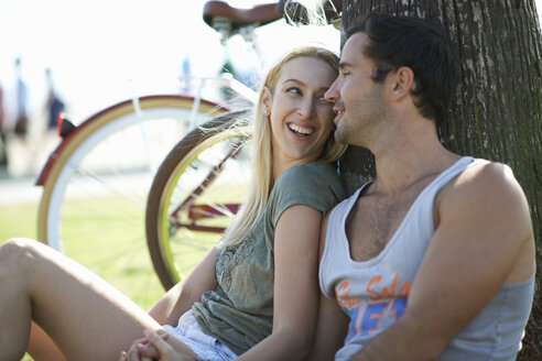 Cycling couple sitting holding hands at Venice Beach, Los Angeles, California, USA - ISF06647