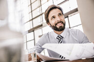 Bearded businessman with paperwork looking away smiling - CUF17957