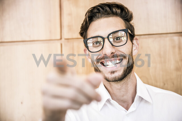 Young man wearing glasses pointing at camera smiling - CUF17996