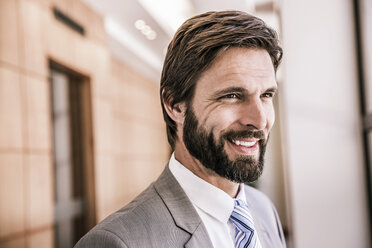 Bearded business man looking away smiling - CUF18002