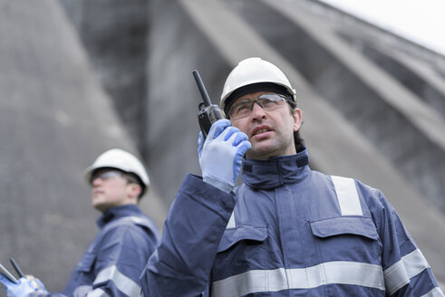 Worker using walkie talkie at foot of dam at hydroelectric power station - CUF18005