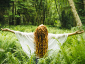Rear view of young woman with long red hair with arms open amongst  forest ferns - ISF06655