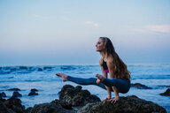 Young woman practicing yoga pose on rocks at beach, Los Angeles, California, USA - ISF06703