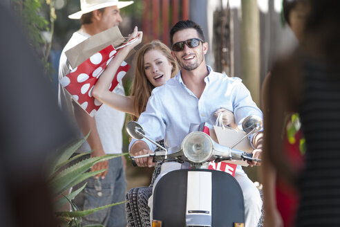 Couple with shopping bags riding on moped - ISF06814