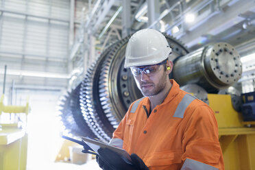 Worker with digital tablet in front of gas turbine in gas-fired power station - CUF18090