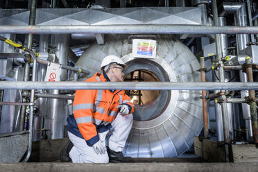 Worker looking into condenser in gas-fired power station - CUF18138
