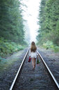 Teenage girl, walking along train track, holding red shoes and flowers, rear view - ISF06836