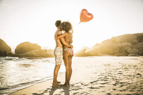 Couple with heart-shaped balloon on beach - CUF18350