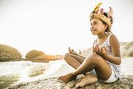 Girl practising yoga on rock - CUF18365
