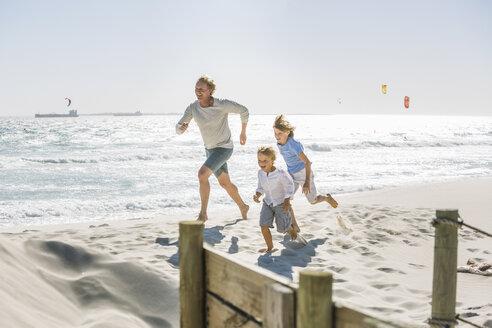 Father and children running on beach - CUF18371