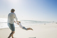 Father swinging son on beach - CUF18383