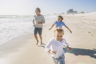 Father and children running on beach - CUF18386
