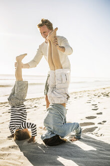 Father helping sons with handstand on beach - CUF18401