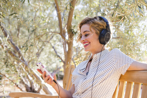 Mid adult woman sitting on bench, wearing headphones, looking at smartphone, smiling - ISF06928