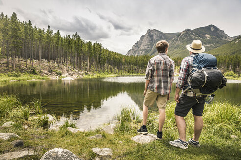 Rear view of father and son looking at view of mountain over Greenough lake, Red Lodge, Montana, USA - ISF06952