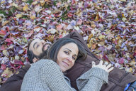Couple lying on autumn leaves in garden - ISF07066