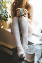 Young woman sitting on windowsill, holding tea cup, low section - ISF07079