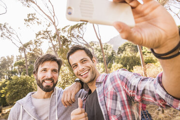 Two men taking smartphone selfie whilst camping in forest, Deer Park, Cape Town, South Africa - CUF18813