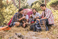 Four male friends relaxing with beer bottles in forest camp, Deer Park, Cape Town, South Africa - CUF18816