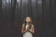 Portrait of long blond haired girl with eyes closed and hands together in misty forest - ISF07098