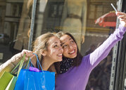 Young female adult twins in city taking selfie on smartphone with shopping bags - ISF07101